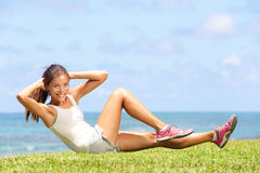 Exercising fitness woman doing sit ups outside. During crossfit exercise training. Happy fit girl doing side crunches with elevated legs while smiling happy Stock Photography