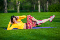 Exercising fitness woman sit ups outside during. Push ups or press ups exercise by young woman. Girl working out on grass crossfit strength training in the glow Royalty Free Stock Images