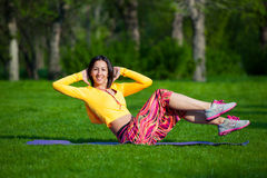 Exercising fitness woman sit ups outside during. Push ups or press ups exercise by young woman. Girl working out on grass crossfit strength training in the glow Royalty Free Stock Photo
