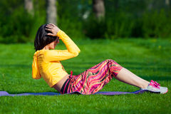 Exercising fitness woman sit ups outside during. Push ups or press ups exercise by young woman. Girl working out on grass crossfit strength training in the glow Royalty Free Stock Photos