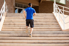 Exercising in a flight of stairs. Young man going up a flight of stairs as part of his workout Stock Images