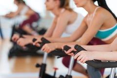 Exercising on gym bikes. Royalty Free Stock Photos