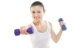Exercising with hand weights. Asian woman exercising with hand weights. Photographed in studio Stock Photo