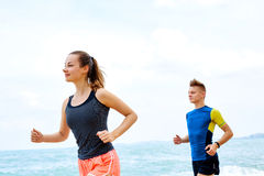 Exercising. Happy Couple Running On Beach. Sports, Fitness. Heal. Exercising. Happy Smiling Sporty Runner Couple Running On Beach. Athletic Woman And Fit Man Stock Photos