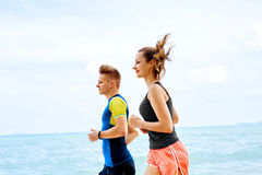 Exercising. Happy Couple Running On Beach. Sports, Fitness. Heal. Exercising. Happy Smiling Sporty Runner Couple Running On Beach. Athletic Woman And Fit Man Royalty Free Stock Photography