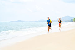 Exercising. Happy Couple Running On Beach. Sports, Fitness. Heal. Exercising. Happy Smiling Sporty Runner Couple Running On Beach. Athletic Woman And Fit Man Stock Images