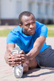 Exercising before jogging. Young african decsent men doing his o Royalty Free Stock Images