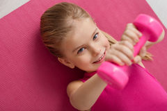 Exercising is the key to health life. Ready to show skills. Close-up shot of lovely little girl smiling and lying on the floor with tiny kettlebell in her hands Stock Photo