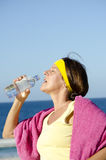 Exercising mature woman drinking water beach Stock Images