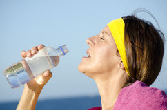 Exercising mature woman drinking water ocean Stock Image