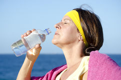 Exercising mature woman drinking water outdoor Royalty Free Stock Photo