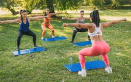 Exercising In Nature. Beautiful girlfriends doing exercise in the park with female fitness trainer. Selective focus Stock Image