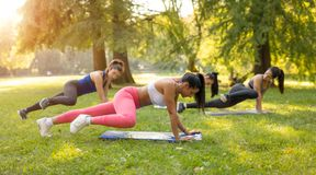 Exercising In Nature. Beautiful girlfriends doing exercise in the park with female fitness trainer. Selective focus Royalty Free Stock Photos