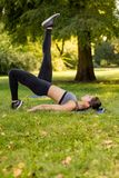 Exercising In Nature. Beautiful young woman doing exercise in the park Stock Photo