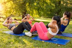 Exercising In Nature. Four beautiful female friends doing sit-up in the park. Selective focus Royalty Free Stock Photo