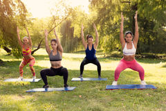 Exercising In Nature. Four beautiful female friends doing squats exercise in the park Royalty Free Stock Images