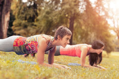 Exercising In Nature. Two beautiful women doing plank exercise in the park. Selective focus Stock Image