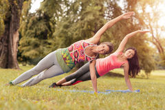 Exercising In Nature. Two beautiful women doing plank exercise in the park. Selective focus Royalty Free Stock Images