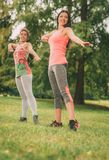 Exercising In Nature. Two beautiful women doing stretching exercise in the park Royalty Free Stock Photo