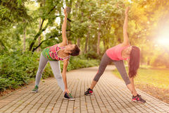 Exercising In Nature. Two beautiful women doing stretching exercise in the park Stock Images
