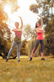 Exercising In Nature. Two beautiful women doing yoga in the park Royalty Free Stock Photography