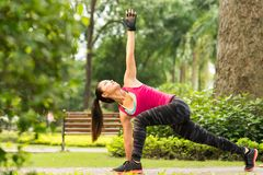 Exercising in park. Vietnamese girl exercising in park doing revolved side angle pose Royalty Free Stock Photos