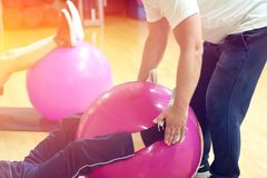 Exercising with personal trainer on large stability ball in studio fitness back