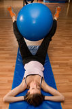 Exercising with a Pilates Ball. A woman exercising with a pilates ball between her legs, which are suspended in the air Stock Photo