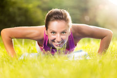 Exercising push-ups. Cute young woman doing push-ups in the park royalty free stock photo