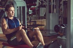 Exercising on Rowing Machine. Confident young sportsman listening to music on headphones and doing exercise on rowing machine, interior of modern gym on royalty free stock photo