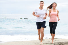 Exercising running couple jogging on beach. Runners training on sand by the ocean smiling happy in full body length. Interracial fit fitness couple, Asian Stock Photography
