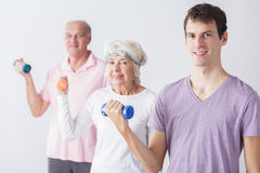 Exercising with seniors. Young men exercising with active happy seniors Royalty Free Stock Photography