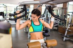 Exercising on Shoulder Press Machine. Attractive sporty woman doing exercise on shoulder press machine while focused on intensive workout at spacious modern gym royalty free stock photos
