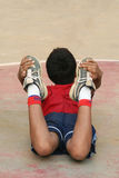 Exercising Sports Boy. A young sports boy (10-12) doing one of the exercises in a warm-up session Royalty Free Stock Photography