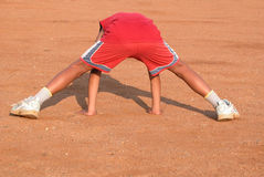 Exercising Sports Boy. A young sports boy (10-12) doing one of the exercises in a warm-up session Stock Photography
