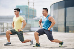 Exercising sporty men. Concentrated sporty young people doing exercising on rooftop Stock Photo
