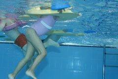 Exercising underwater. Underwater picture of children exercising on a swimming pool Stock Image