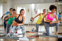 Exercising with weight for arms. Exercisers group in gym doing exercises with weight for arms Royalty Free Stock Photos