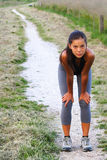 Exercising woman. Workout on trail. Woman resting of running outside. Beautiful mixed race young woman Royalty Free Stock Images