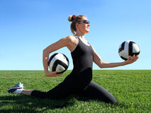 Exercising woman. Young pretty woman exercising on green grass Stock Image