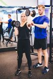 Exercising woman assisted by personal trainer. Exercising women assisted by personal trainer. Working out. Fitness coach royalty free stock image