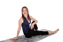 Exercising woman sitting on floor, resting. A beautiful young woman in an exercising outfit sitting on a towel on the Royalty Free Stock Photography