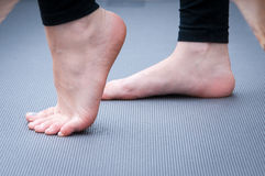 Exercising. On the yoga mat with feet in focus Stock Photos