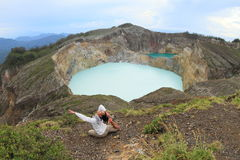 Exercising yoga on volcano. Papuan young woman exercising yoga Mermaid pose in front of light blue or white acid-saline lake Tap - Tiwu Ata Polo - and dark green Stock Image