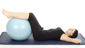 Exercising young woman with big blue ball Royalty Free Stock Image