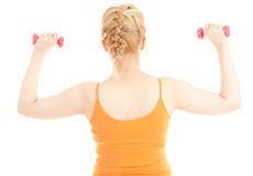 Exercising young woman with small dumbbells Royalty Free Stock Images