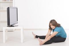 Exercisng de la mujer en casa foto de archivo