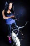 Exercitando na bicicleta, trabalhando no portátil Fotografia de Stock