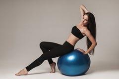 exersicing与健身球的年轻可爱的妇女 免版税库存图片