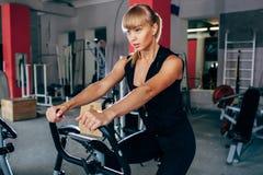 exersizing的自行车的白肤金发的妇女 免版税图库摄影